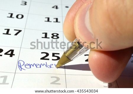 human hand writing remember on a date on a white calendar - stock photo