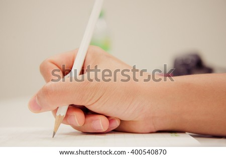human hand writing something on the paper in pastel tone - stock photo