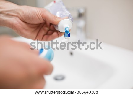 Human hands applying toothpaste on an electric blue toothbrush - stock photo