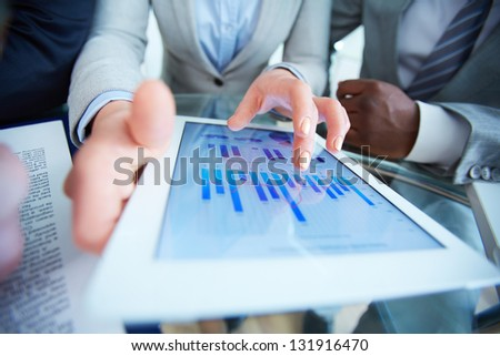 Human hands during discussion of business document in touchscreen at meeting - stock photo