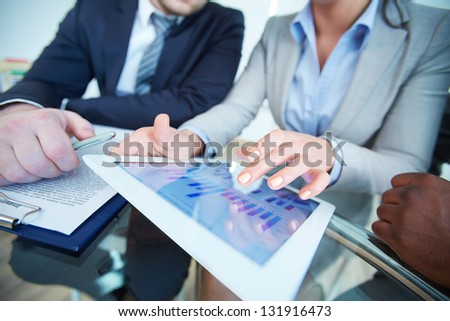 Human hands during discussion of business document in touchscreen at meeting