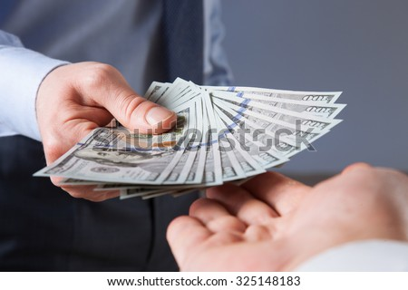 Human hands exchanging money on blue background, closeup shot