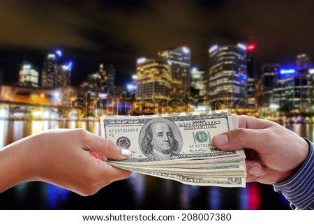 Human hands exchanging money on night city background - stock photo