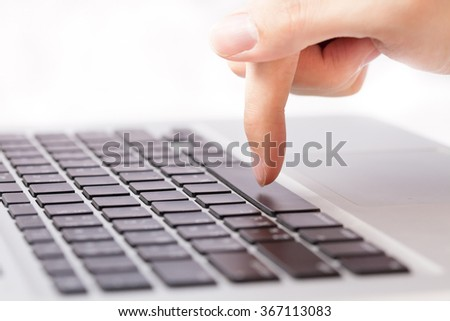 Human hands going to press a button on keypad in white isolated background