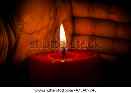 Human hands hold heart shaped burning candle against dark background