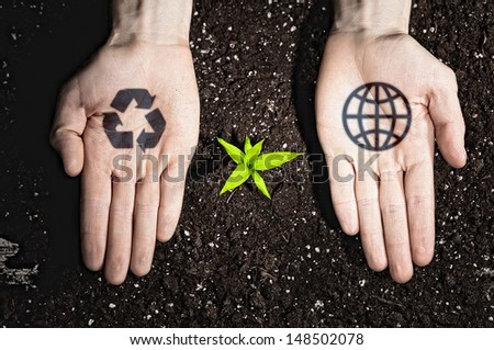 Human hands holding a green sprout and ecology symbols - stock photo