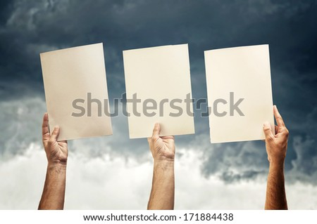 Human hands holding blank papers, stormy sky in the background.