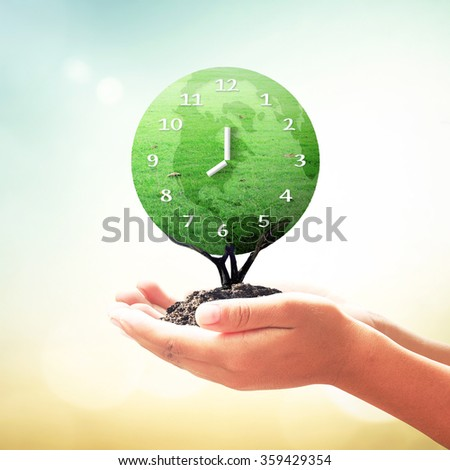 Human hands holding clock of earth grass tree on blurred beautiful sunset background. Ecology, World Environment Day, Investment, CSR, Health Care, Healthcare, Insurance Agent, Organ Donation concept - stock photo
