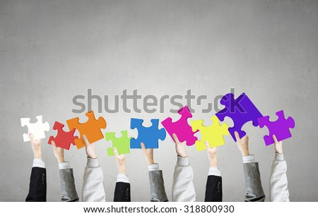 Human hands holding colorful jigsaw puzzle elements - stock photo