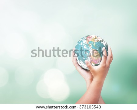 Human hands holding green globe on beautiful nature background. Day World CSR Earth Hour Trust Global Service International Creativity Innovation concept. Elements of this image furnished by NASA - stock photo