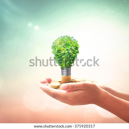 Human hands holding lightbulb of tree on golden coins over blurred nature background. Ecology, World Thinking Day, Eco Friendly, Spring, Environment, Go Green, Saving, Technology concept.
