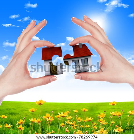 human hands holding model of a house against nature background