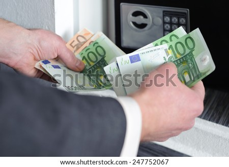 Human hands holding money against a background of safe