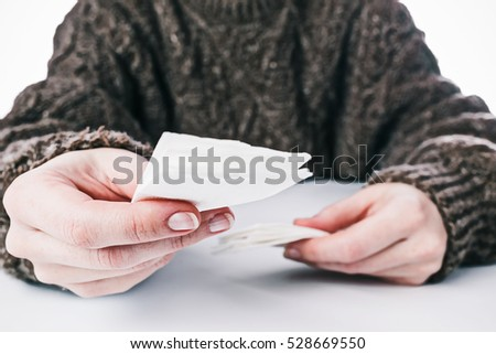Human hands holding paper hankie directing to the viewer to dry tears or nose. Care concept. Selective focus. Front view
