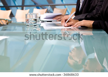 Human hands holding pen and making notes during conference - stock photo