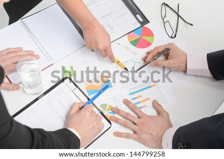 Human hands holding pens and papers, making notes in documents,  on the table - stock photo