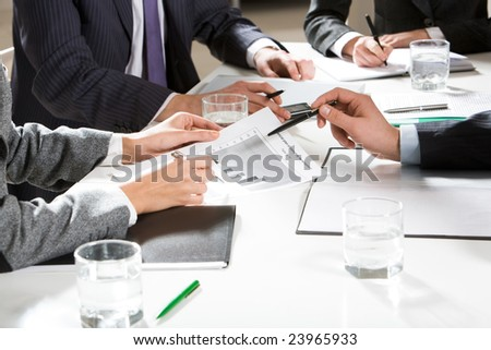 Human hands holding pens and papers, making notes in documents, touching the phone during business meeting - stock photo