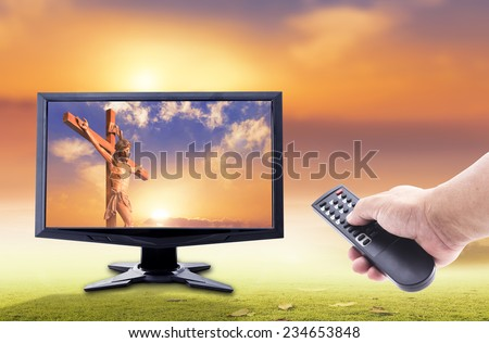 Human hands holding remote and monitor display Jesus christ with the cross on sunset over the actual location. - stock photo