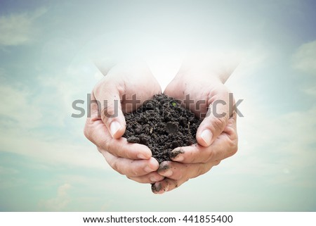 Human hands holding soil emerges from the sky in the background blurred.Environment Day concept. Ecology concept.  - stock photo