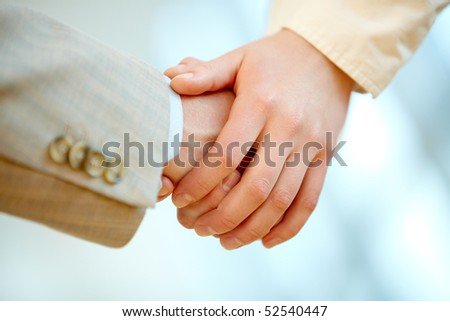 Human hands holding those of business partner symbolizing help and support - stock photo