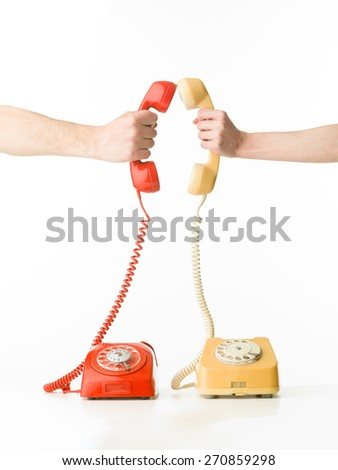 human hands holding two phone receivers facing each other, on white background - stock photo