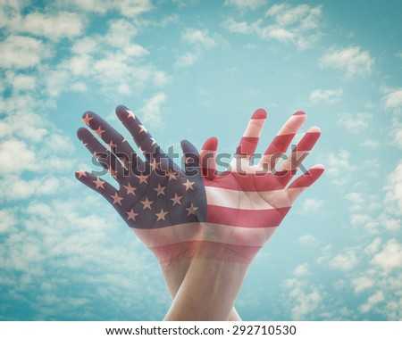 Human hands in eagle bird form with double exposure of the United States of America flag pattern against vintage style blue sky background with soft clouds: USA Independence day and flag day concept   - stock photo