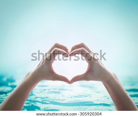 Human hands in heart shape showing love and friendship on blurred wavy clean blue water background: Saving water and natural environment sea ocean concept/ campaign/ idea: Happy valentine's day  - stock photo