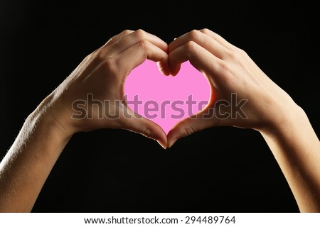 Human hands making heart on black background - stock photo