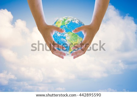 Human hands on both sides holding the world sky in the background blurred.Environment Day concept. Ecology concept.Environment Day concept. Ecology concept..Elements of this image furnished by NASA. - stock photo