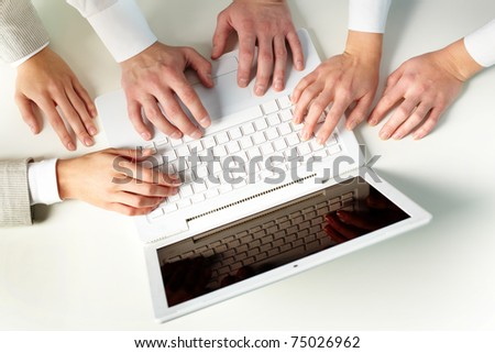Human hands on keypad of laptop at workplace - stock photo