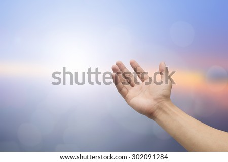 Human hands open palm gesture on blurred sea background: hand receiving power form god.religious concept.  - stock photo