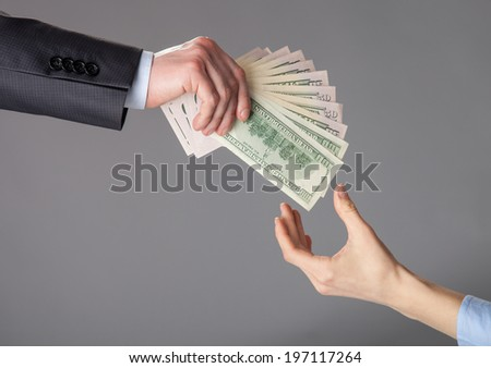 Human hands passing fan of dollar banknotes on grey background - stock photo