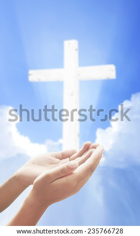 Human hands praying over the cross and amazing light. - stock photo