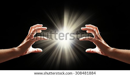 Human hands with light on black background - stock photo