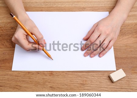 Human hands with pencil writing on paper and erase rubber on wooden table background - stock photo