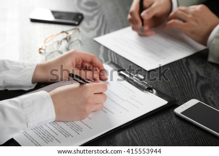 Human hands with pens working with documents at the desk closeup - stock photo