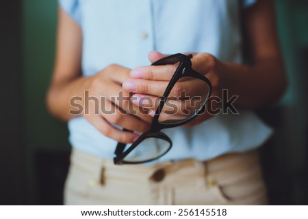 Human hands woman holding retro style eyeglasses - stock photo