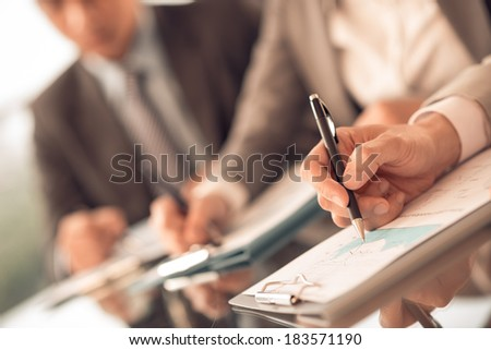 Human hands writing something at the business seminar on the foreground  - stock photo