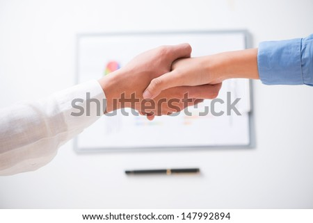 Human handshaking after signing a contract viewed below - stock photo