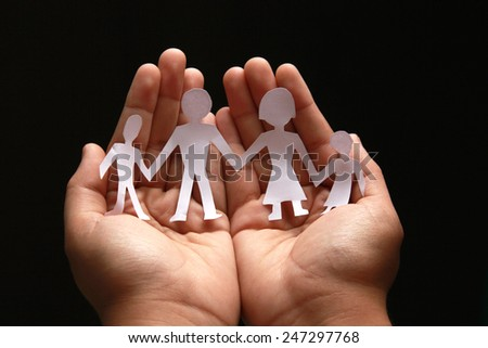 human holding little paper cutout family, happy family concept