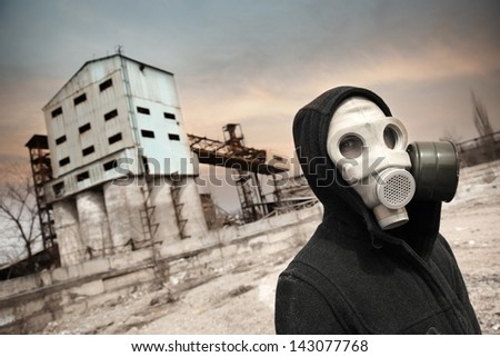 Human in gas mask outdoors and industrial factory on a background - stock photo