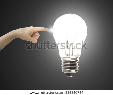 Human index finger touching lightbulb with bright light, on black background. - stock photo