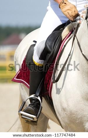 human leg on the horseback - stock photo