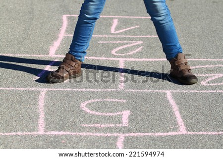 Human legs in jeans and boots stand on asphalt lined to play hopscotch with shadow outdoor in sunny day - stock photo