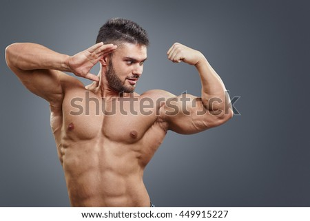 Human Muscle Bicep Growth concept. Strong man surprised of his muscular arm isolated on grey background.