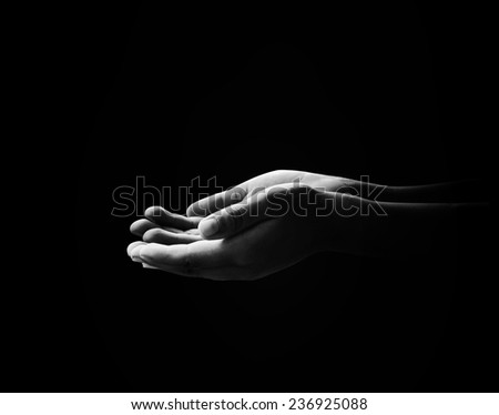 Human open empty hands with palms up, over black background. - stock photo