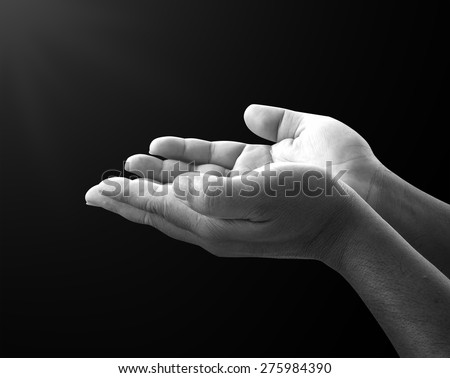 Human open empty hands with palms up, over black background.