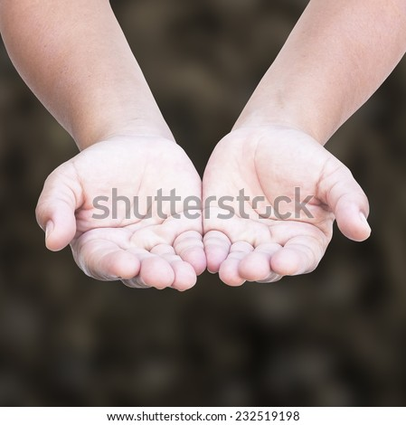 Human open empty hands with palms up over blurred ground background. - stock photo