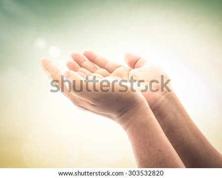 Human open empty hands with palms up, over blurred nature background. Christmas Health Care Worship Repentance Reconcile Adoration Glorify Redeemer Pentecost Holy Spirit Whit Monday concept.