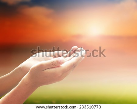 Human open empty hands with palms up over blurred sunset background. - stock photo